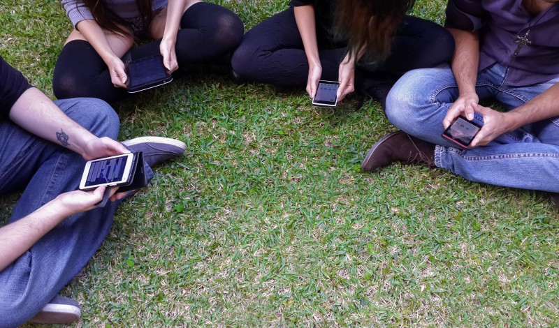 Young adult friend view social media on smart phones and tablet