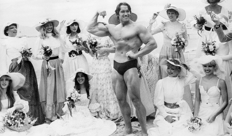 Arnold Schwarzenegger, the film actor who first became famous as Mr Universe for his magnificent physique, on Cannes beach during the Film Festival with the girls from the Folies Bergere.    (Photo by Keystone/Getty Images)
