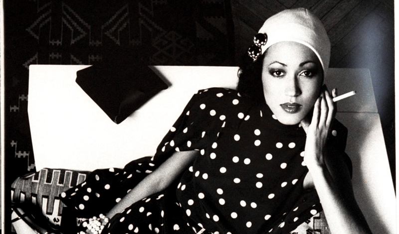 Model Pat Cleveland, reclining on a sofa and holding a cigarette, wearing a polka dot print sleeveless dress and matching shirt-jacket by Chuck Howard, with a white skull cap by Adolfo. (Photo by Bob Stone/Conde Nast via Getty Images)