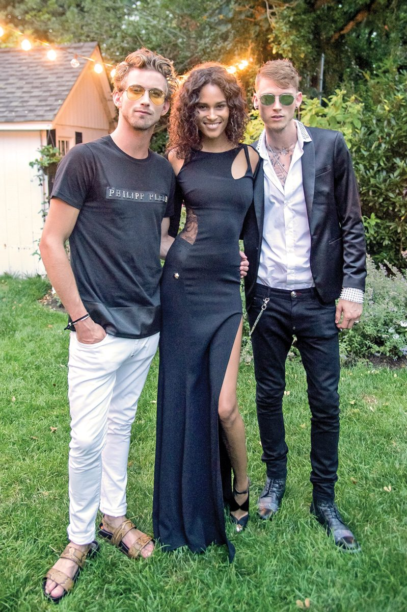 EAST HAMPTON, NY - JULY 16: Model RJ King, Model Cindy Bruna and Rapper Machine Gun Kelly attend Daily Front Row's Philipp Plein Dinner on July 16, 2016 at the Maidstone in East Hampton, New York. (Photo by Mark Sagliocco/Getty Images)